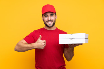 pizza delivery man with work uniform picking up pizza boxes over isolated yellow background with thumbs up because something good has happened