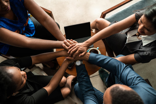 Top view of black african business team with hands stacked together in unity and trust.