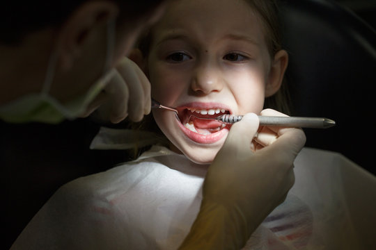 Scared little girl at the dentists office, in pain during a treatment.