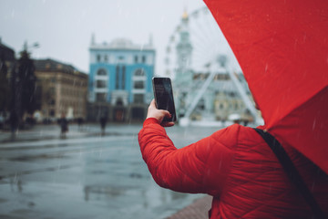 Girl with red umbrella taking photos in the rain. Woman traveler take pictures on rainy day