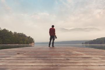 Landscape photographer at lake pier in misty morning Fotobehang