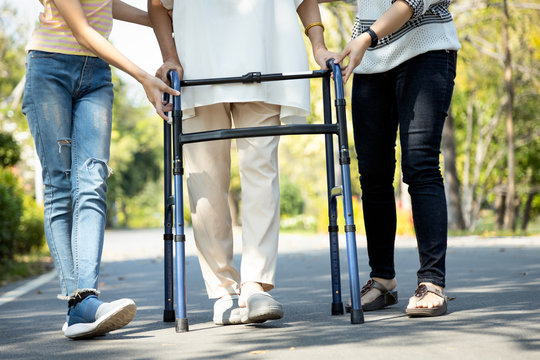Asian senior woman use walking aid during rehabilitation after physical therapy or knee surgery, elderly people practice walking,exercising with walker for safety, family help,care,support her mother
