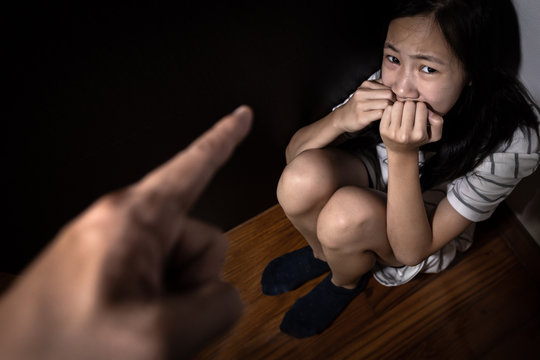 Sad asian child girl sit on floor,feel fear,pain,cry, stop physical abuse and domestic violence, angry man or father scolds frightened daughter,campaign against violence and aggression concept.