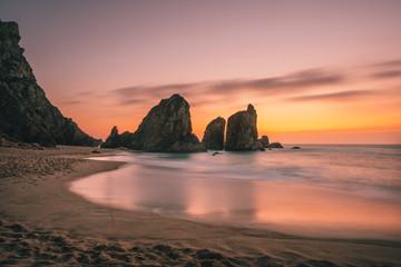 Zelfklevend Fotobehang Diepbruine Ursa Beach near Cape Roca at Atlantic Ocean coast in Portugal. Sand beach with sea stacks in evening golden sunset sky