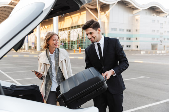 Image of young businesslike man and woman putting luggage in car trunk