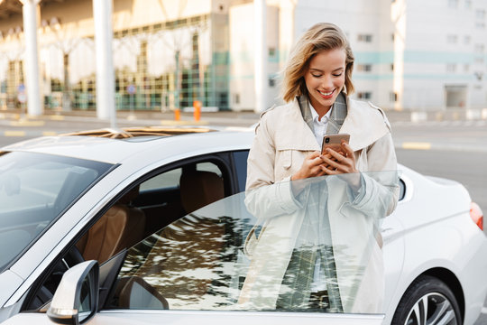 Image of businesslike woman standing by car and using cellphone outdoors