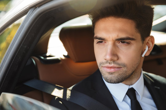 Image of young caucasian businesslike man in suit riding in car