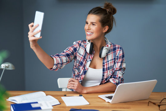 Female student learning at home and taking selfie