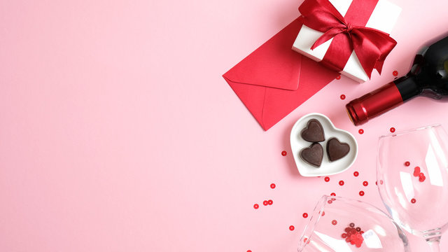 Valentine's day background with wine bottle, gift box, glasses, heart shaped candies, red paper envelope and confetti on pink background. Greeting card template for Valentines Day. Flat lay, top view