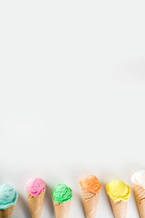Colorful pastel ice cream with waffle cones, white background, copy space top view