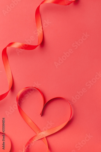 Heart shaped ribbon on red background with copy space. Valentine's Day, Women's Day, Birthday, Mother's Day holiday greeting card concept. Copy space, top view, flat lay. Vertical orientation