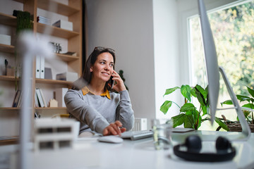 Attractive businesswoman sitting at the desk indoors in office, using smartphone.