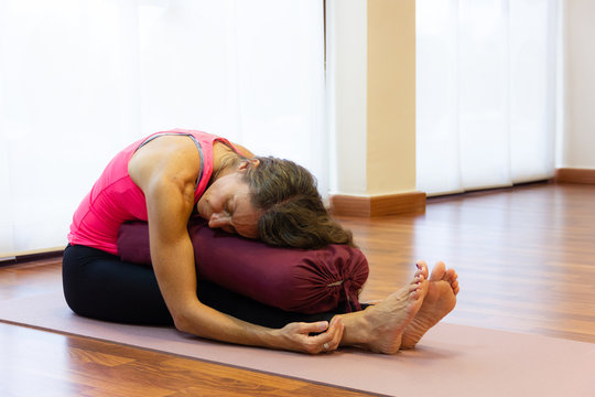 Middle aged woman on pink tank top in paschimottanasana pose resting chest on bolster at bright studio. Female yogi on seated forward bend asana. Therapeutic exercise concept