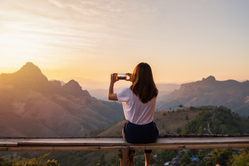 Young woman traveler taking photo with smart phone at sunset over the mountain