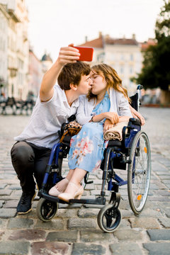 Young Couple taking Selfie. Pretty happy young disabled woman in wheelchair kissing with her young boyfriend and smiling while taking selfie with him In The City