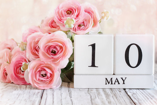 White wood calender blocks and pink ranunculus flowers with the date May 10 th for Mother's Day. Selective focus with blurred background.