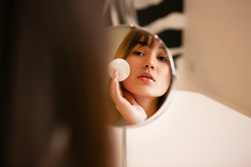 Portrait of a beautiful girl with mirror, makeup process, beauty, skin care.