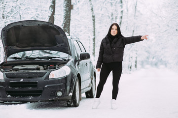 brunette girl waiting for help on the road near a broken car. road assistance