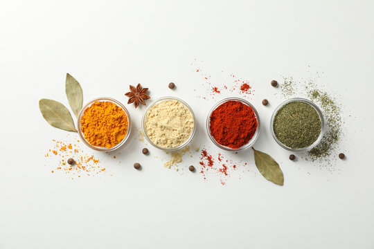 Bowls with different spices on white background, top view