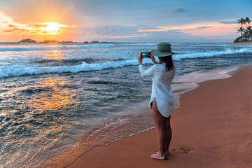girl taking pictures of sunset with smartphone