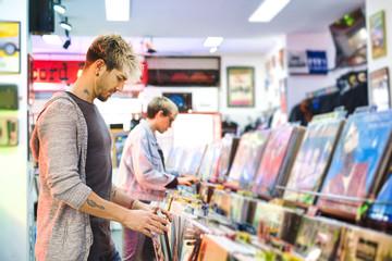 Spoed Foto op Canvas Muziekwinkel Young Man Choosing Vintage Vinyl LP In Records Shop