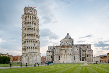 Calm evening at Pisa touristic center. Piazza del Duomo with fanous cathedral and tilting tower. Pisa, Italy.