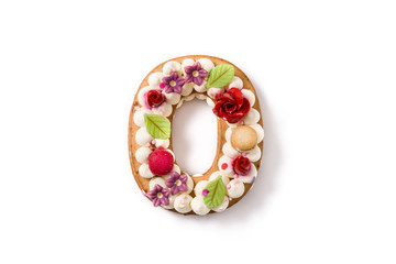 Number zero cake decorated with flowers  and macarons isolated on white background.
