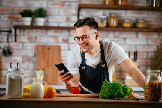 Young man in kitchen. Chef using phone while making food.