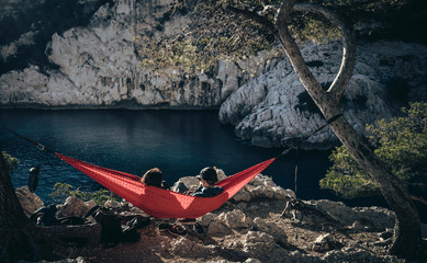 Couple sitting in red hammock enjoying the scenery