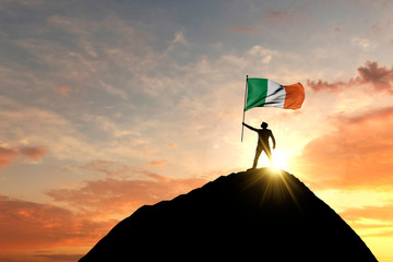 Irish flag being waved at the top of a mountain summit. 3D Rendering
