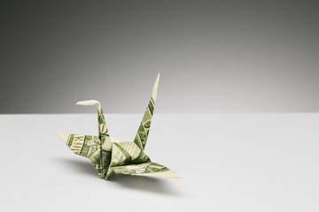 Origami crane made of dollar bill on counter