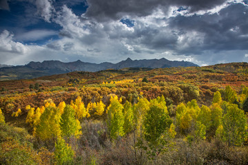 Clouds over yellow autumn trees in valley below mountains, Dallas Divide, Colorado, United States,