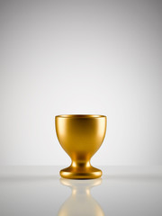 Empty golden egg cup holder against white background