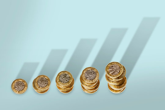 Ascending stacks of pound coins with bar graph growth shadow