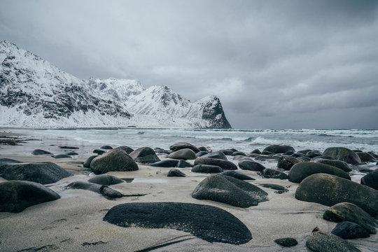 Rocks on snowy, remote beach, Lofoten Islands, Norway