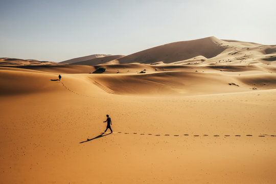 Man walking in sunny, sandy desert, Sahara, Morocco