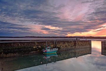 Fishing boot moored along jetty wall under dramatic sunrise sky