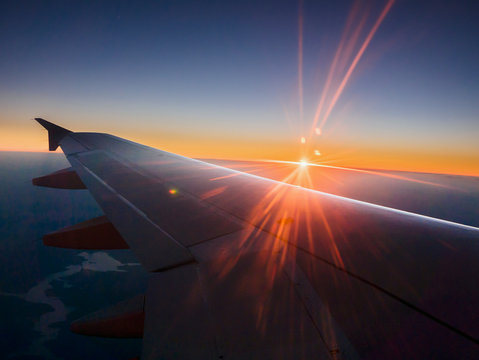 Sunset behind airplane wing in sky