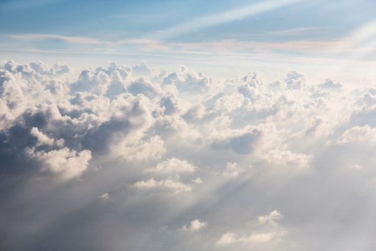 Aerial view sunbeams over fluffy white clouds