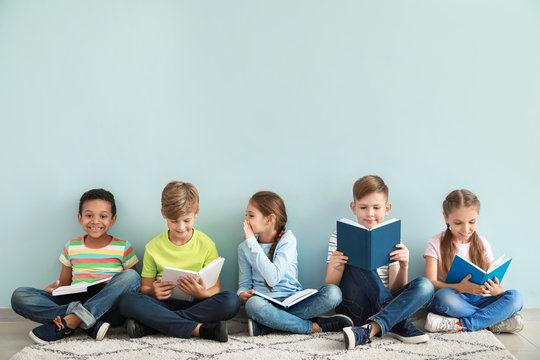 Cute little children reading books on color background