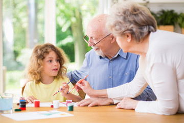 Grandparents painting a picture with paints with their grandson