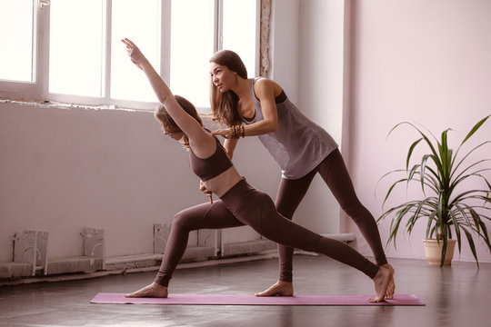 Yoga instructor training group of women on fitness studio background. Healthy lifestyle. Strength exercise. Yoga class, workout. Sport background.