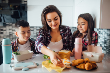 Mother making breakfast for her children in the morning and a snack with lunch box for school.