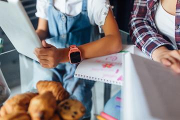 Children hands doing homework using digital tablet, close up photo, pink smart watches at kid hand.