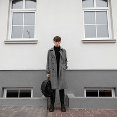 Attractive young man in a long plaid fashionable coat in black stylish boots with a cool leather backpack stands on the street near a white building. Handsome european guy outdoors. Youth menswear.