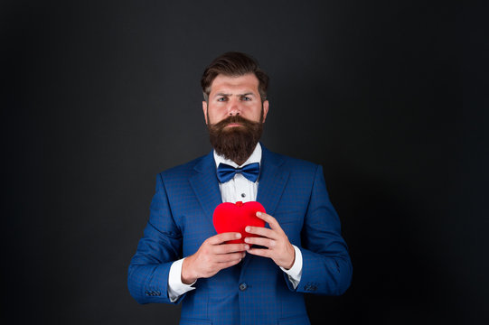 happy valentines day. tuxedo man with red heart. love and romance. ready for date. brutal bearded hipster in formal outfit. confident and successful businessman in suit with bow tie