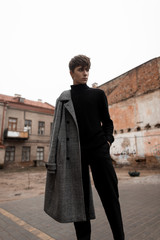 Young European man model with a fashionable hairstyle in a stylish gray plaid coat in jeans in a black vintage sweater stands outdoors on the street among the buildings. Nice trendy european guy.