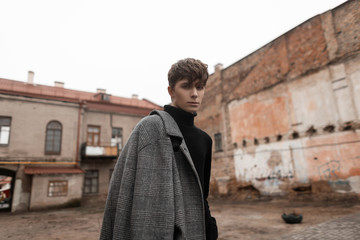 Portrait of a European young man in stylish classic outerwear with a fashionable hairstyle walks along a city street near old buildings. Handsome trendy guy model. Elegant seasonal look. Menswear.