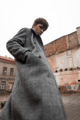 In a fashionable gray plaid long coat a handsome stylish young man with a trendy hairstyle is standing on the street. Attractive guy model in seasonal clothes poses outdoors. New collection menswear.