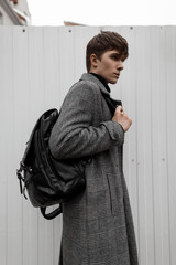 European young man in a trendy gray plaid coat with a stylish hairstyle with a leather black backpack stands in the city near a metal white wall. Attractive guy is a fashion model.Fashionable menswear